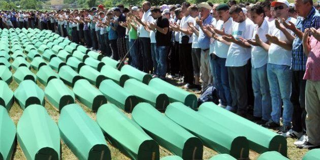 Bosnian Muslims, survivors of Srebrenica 1995 massacre pray near body caskets of their relatives, layed...