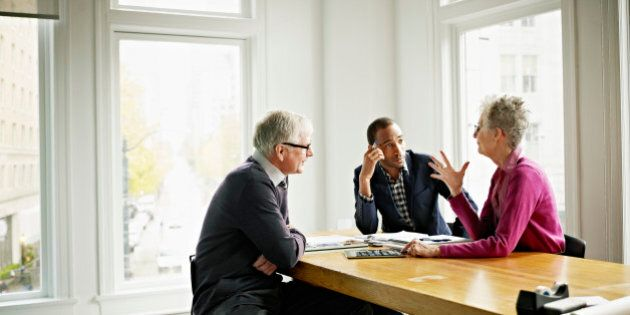 Group of three coworkers in discussion in conference