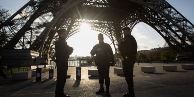 French armed police officers stand guard at the Eiffel Tower in Paris, France on Sunday, Nov. 15, 2015....