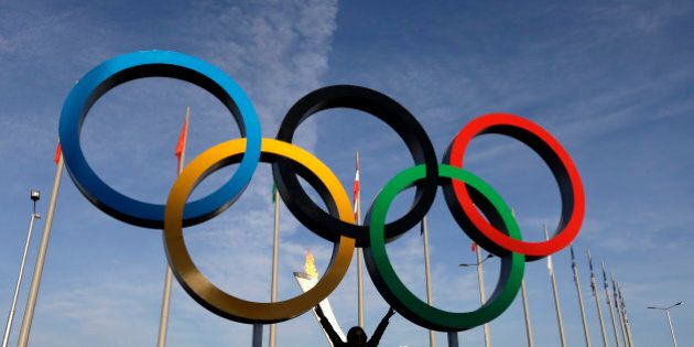 A spectator poses for a photo under the Olympic Rings at the 2014 Winter Olympics, Wednesday, Feb. 12, 2014, in Sochi, Russia. The Winter Olympics are in full swing, but warm temperatures in the Black Sea resort town of Sochi made heavy coats and scarves unnecessary on Wednesday. (AP Photo/Mark Baker)