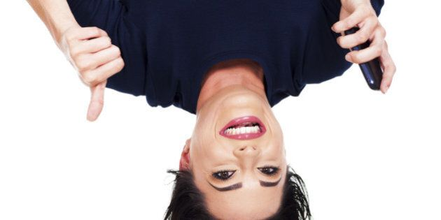 upside down view of young woman holding smart phone and giving thumb