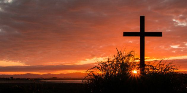 Cross on a hill as the morning sun comes up for the