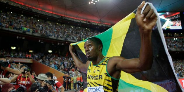 Jamaica's Usain Bolt celebrates after winning the gold medal in the men's 100m ahead of United States'...