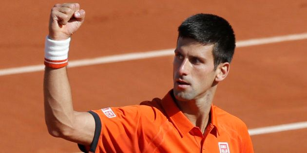 Serbia's Novak Djokovic clenches his fist after scoring a point in the quarterfinal match of the French...