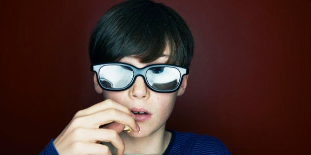 boy with 3d glasses and popcorn looking