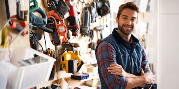 Portrait of a handsome young handyman standing in front of his work