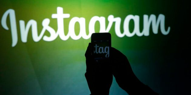 A journalist makes a video of the Instagram logo using the new video feature at Facebook headquarters...