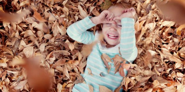 Little girl playing in fall leaves