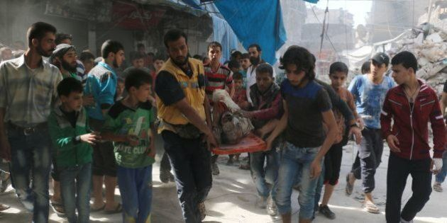 TOPSHOT - Syrians carry the body of a man following air strikes on the rebel-held Fardous neighbourhood...