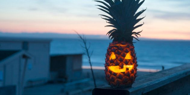 Jack o lantern halloween face carved into pineapple instead of pumpkin. Tropical fruit with ocean in background