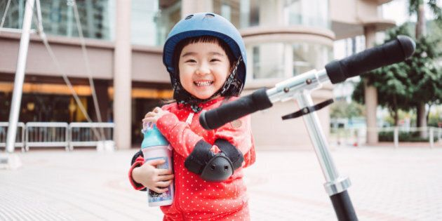 Lovely little girl with a helmet and protective gears smiling joyfully at the camera while holding her water bottle in front of the scooter on the street