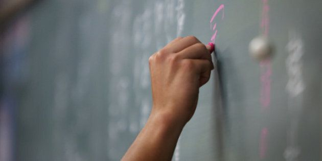 A teacher writes on a chalkboard during a class at the Korean High School in Tokyo, Japan, on Thursday,...