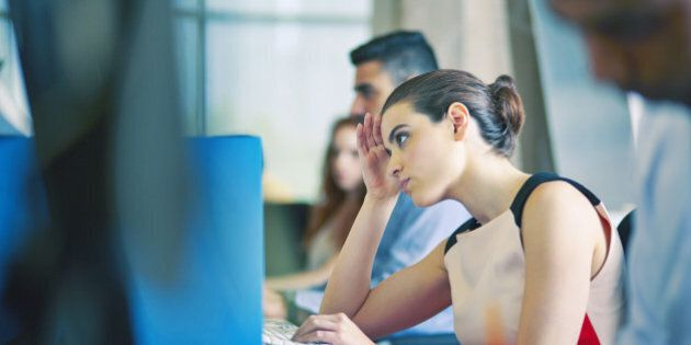 Woman at desk, staring at computer