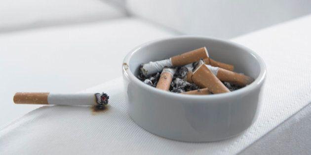 Cigarette burning arm of sofa