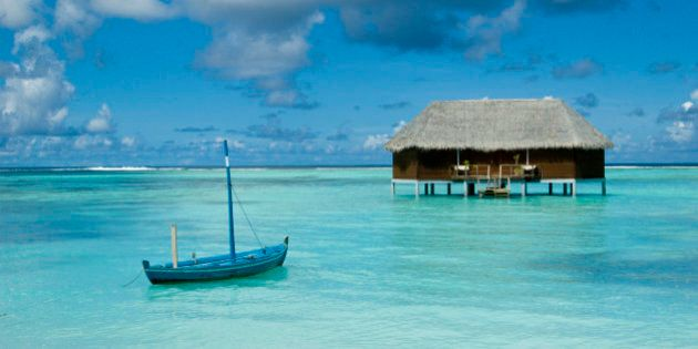 A dhoni (traditional Maldivian boat) floating in a lagoon with an over-water honeymoon bungalow off in the distance, Maldives.