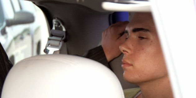 In this photo provided by Montreal Police, Luka Rocco Magnotta is guided into a waiting van after arriving...
