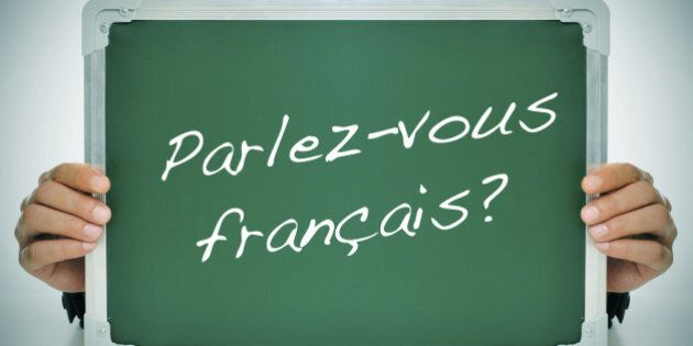 man wearing a suit holding a chalkboard with the question parlez-vous francais? do you speak french?...