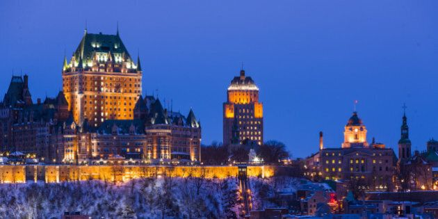 City skyline at night/twilight, showing Chateau Frontenac in winter, viewed from across the Saint Lawrence...