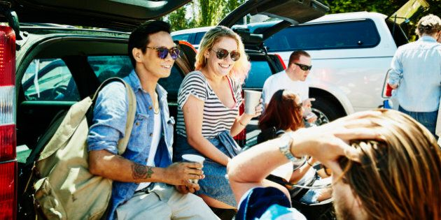 Smiling friends sitting on bumper of car tailgating in stadium parking lot before football
