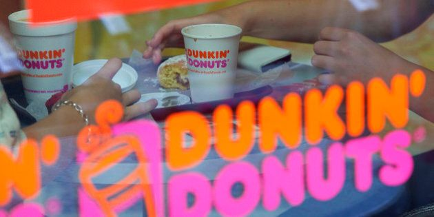Customers sit at a table with their doughnuts and drinks inside a Dunkin' Donuts store, operated by Dunkin'...