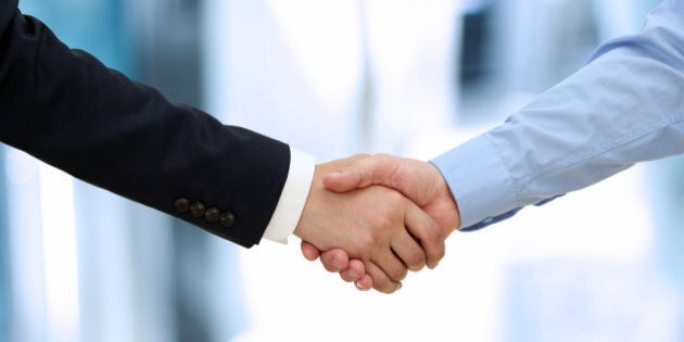 Close-up image of a firm handshake between two colleagues in