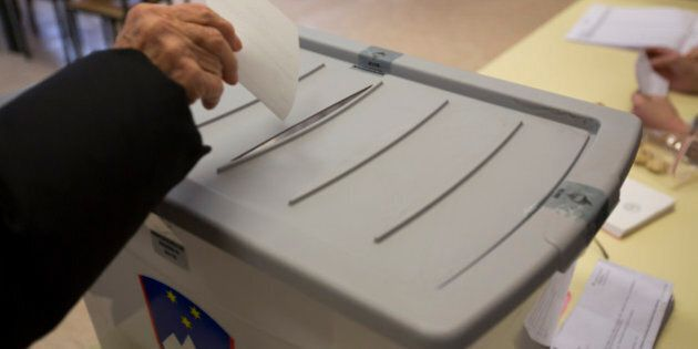 A voter casts his ballot at a a polling station in Ljubljana, Slovenia, Sunday, Dec. 20, 2015. Slovenians...