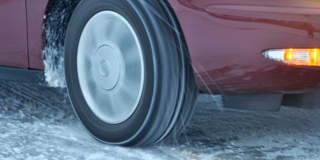 Automobile tire spinning on ice, particles flying, long