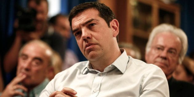 Greece's Prime minister Alexis Tsipras listens to a speech during a gathering at the Agriculture ministry...