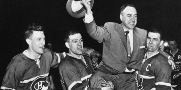 Montreal Canadian's players hoist their coach into the air after winning the Stanley Cup for the second...