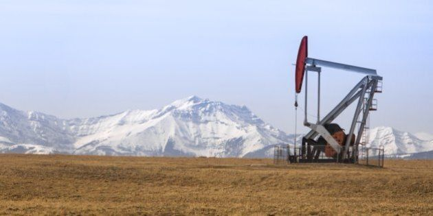 Oil 'donkey' pumps on grass slope below snowy