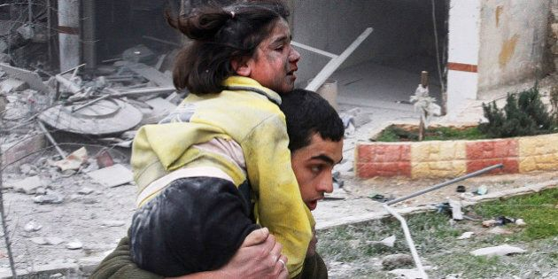 FILE - In this Sunday, Feb. 3, 2013 file photo, Syrian man carries his sister who was wounded in a government...