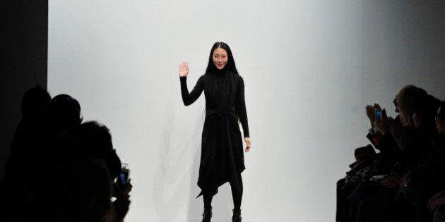 Fashion designer Yiqing Yin waves after the presentation of Leonard's ready-to-wear fall/winter 2014-2015...