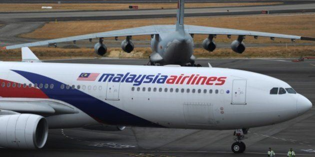 A Malaysia Airlines plane (below) prepares to go onto the runway and pass by a stationary Chinese Ilyushin...