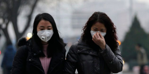 Women wear masks for protection against the pollution as they walk along a street on a polluted day in...