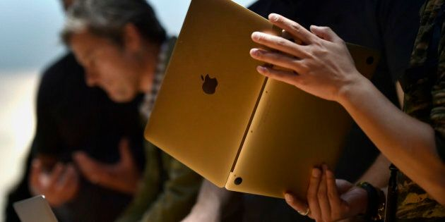 Attendees view the Apple Inc. Macbook laptop during the company's Spring Forward event in San Francisco,...