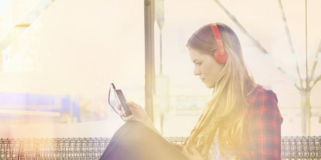 woman at station listening to music with