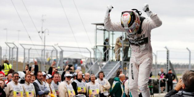 Mercedes driver Lewis Hamilton, of Britain, celebrates after winning the world championship win his victory...