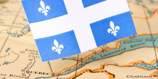 Quebec flag over more that sixty years old map pointing Quebec city. Shallow depth of