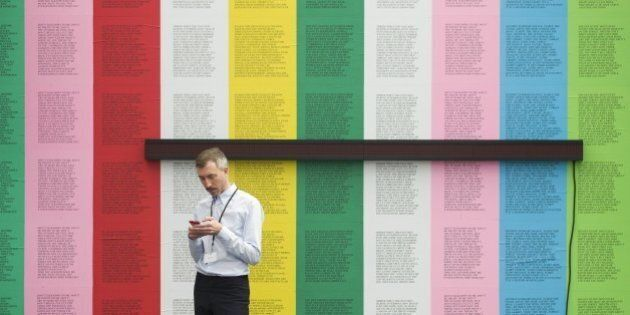 An exhibitor uses his phone standing in front of 'Survival' by US artist Jenny Holzwer at the Frieze...
