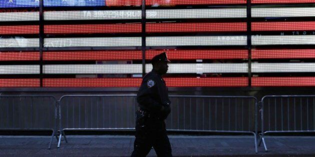 FILE. In this Jan. 8, 2015 file photo, a police officer walks through Times Squarein New York. In bustling...