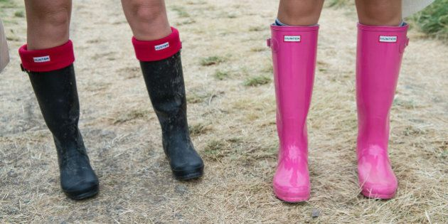 GLASTONBURY, ENGLAND - JUNE 26: Festival goers wear wellington boots in preparation for rain during the...