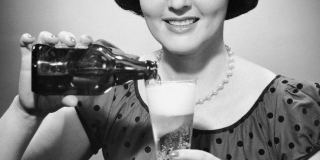 UNITED STATES - CIRCA 1950s:  Woman pouring alcoholic beverage.