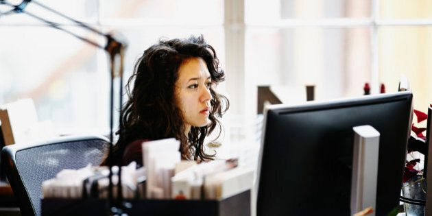 Businesswoman sitting at desk working on computer at workstation in