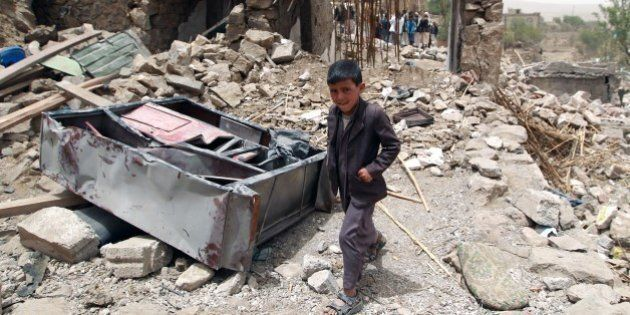 A Yemeni boy walks past the rubble of destroyed houses in the village of Bani Matar, 70 kilometers (43...