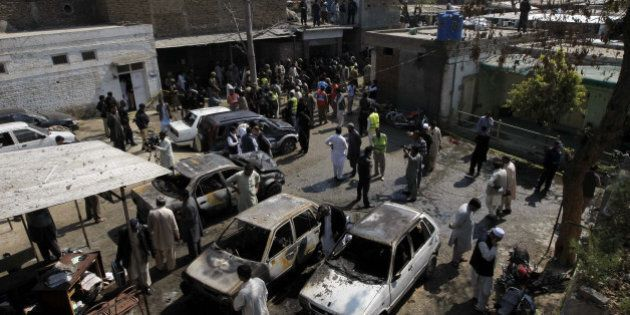 Pakistani security officials inspect the site of a suicide bombing in Shabqadar on March 7, 2016.A suicide...