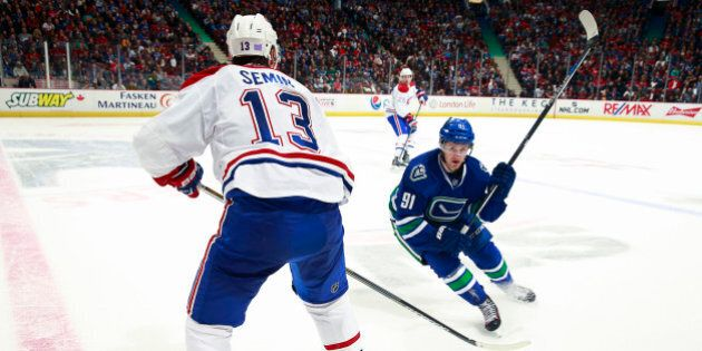 VANCOUVER, BC - OCTOBER 27: Jared McCann #91 of the Vancouver Canucks lines up a check on Alexander Semin...