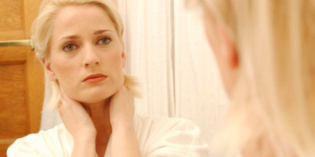 Woman Looking At Her Face In Bathroom