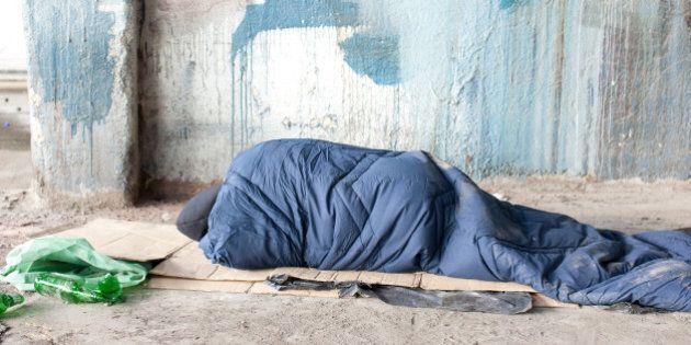 Homeless man sleeping in sleeping bag on