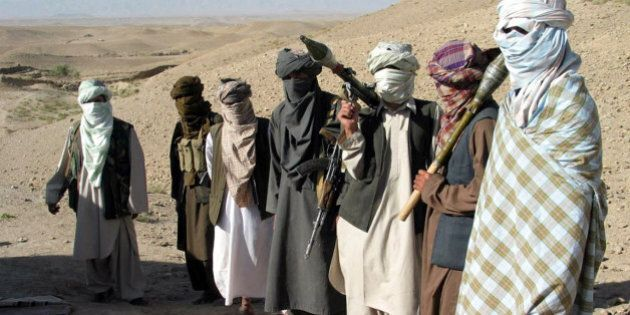 Face-covered militants who they say are Talibans, pose with RPG and AK47 in Zabul province, southern...