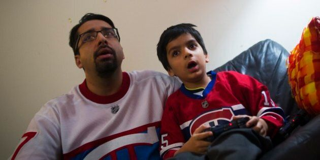 TORONTO, ON - JANUARY 4: Sulemaan Ahmed plays video games with his six year old son Adam Syed Ahmed at...